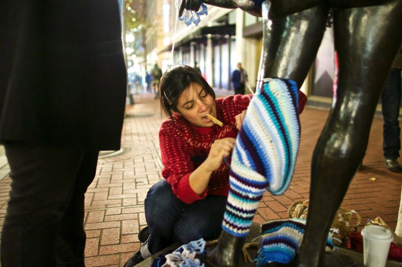 by: TRIBUNE PHOTO: JAIME VALDEZ - Claudia Martinez puts legwarmers on the Kvinneakt statue, part of the wardrobe she and other artists designed and knit in past weeks. The yarn-bombing and other promotions continue through the end of December.