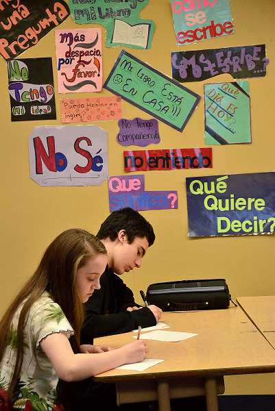 by: VERN UYETAKE - Lake Oswego Junior High eighth-graders Sarah Rourke and Humberto Velazquez take a quiz in Ian Reeves Spanish class.