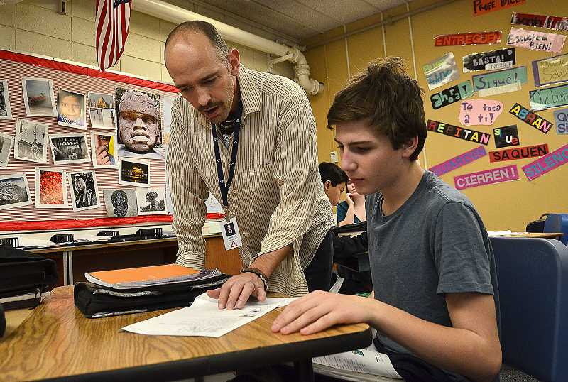 by: VERN UYETAKE - Lake Oswego Junior High teacher Ian Reeves discusses a Spanish lesson with eighth-grader Joe Lantow.