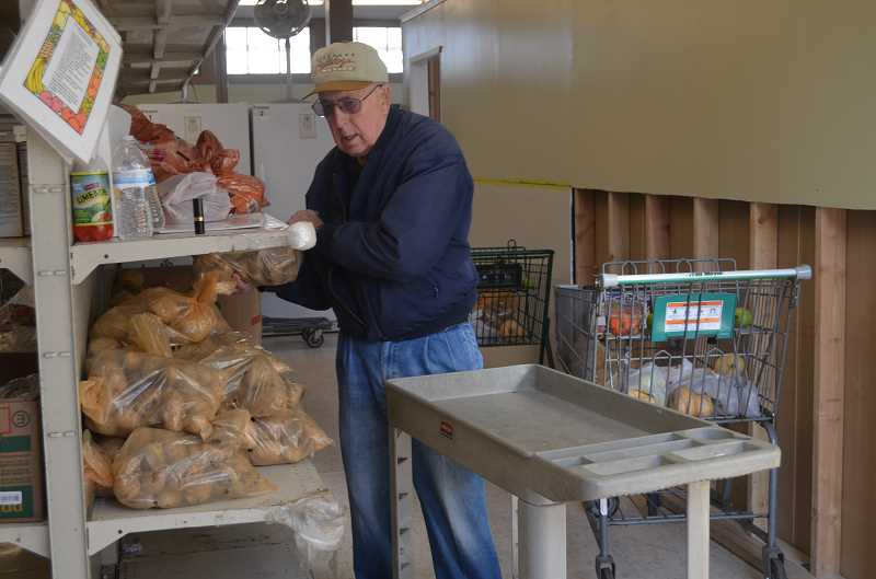 by: JANIS BRENTANO - Loy Kirksey loads potatoes onto shelves of Woodburn AWARE Food Bank. Kirksey has volunteered at the food bank for the past five years.