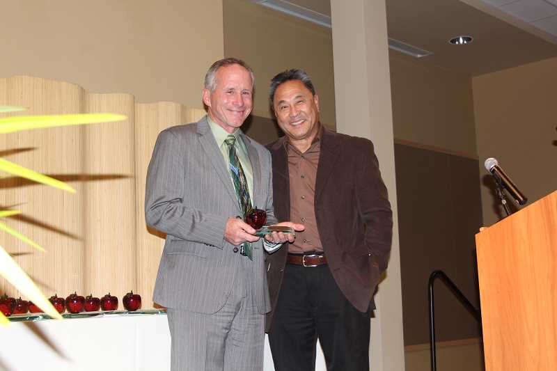 by: NIKKI DEBUSE - Woodburn Health Center hosted the annual Crystal Apple Awards, which saw a special award given to Gervais Superintendent Rick Hensel by Harry Lee Kwai.