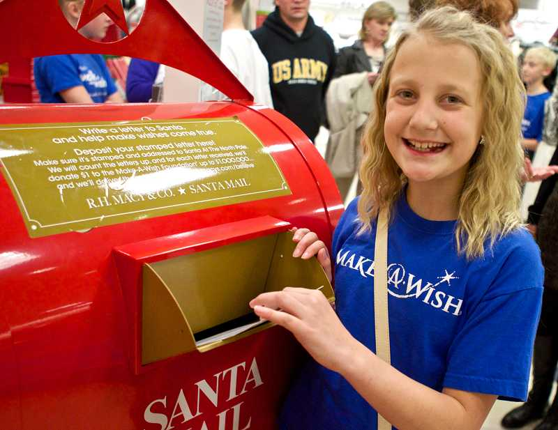 by: TIMES PHOTO: JAIME VALDEZ - Lily Moser puts her letter to Santa in the drop box during Macy's Believe Campaign launch at the Washington Square mall.