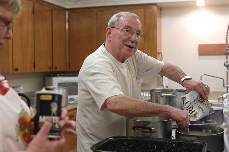 by: TIMES PHOTO: JONATHAN HOUSE - Making more gravy, Dave Dobbins served as the main force in the kitchen at Tigard Church of God's Saturday pre-Thanksgiving feast.