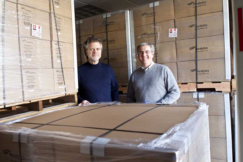 by: TIMES PHOTO: JAIME VALDEZ - Ed Kolasinski and Mark Owen of Puralytics stand amidst boxes of SolarBag water purification packs that are ready to be shipped to the Philippines.