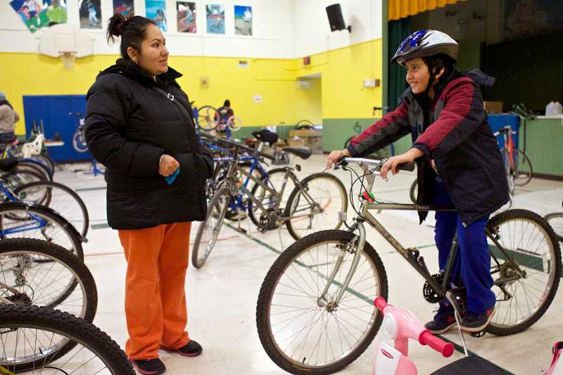 by: TIMES PHOTO: JAIME VALDEZ - Aurora Ortiz Soto watches as her son Ulices, a fifth-grader at William Walker Elementary School, sits on a bike he's interested in during a Bikes For Humanity PDX event at Barnes Elementary School.