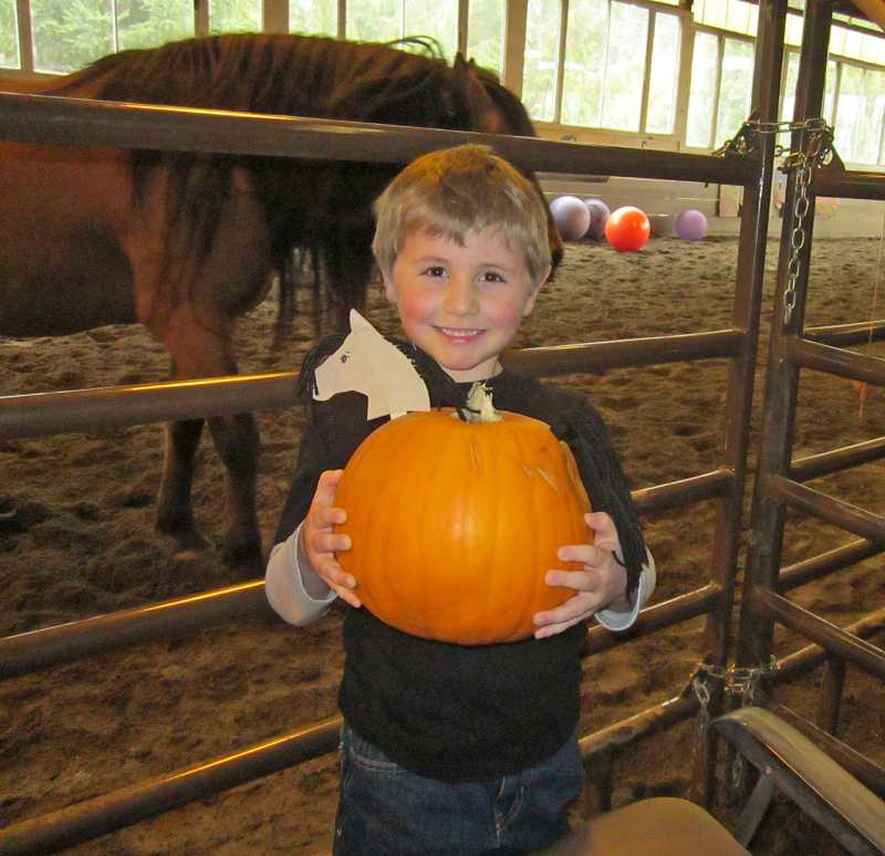 by: BARBARA SHERMAN - Todd Hildebrandt, a kindergartner at Sherwood Charter School, holds his mustang pumpkin outside the arena where various horse events took place at Wild Horse Mountain Ranch's annual Kids, Pumpkins, Music & Mustangs' fundraiser.