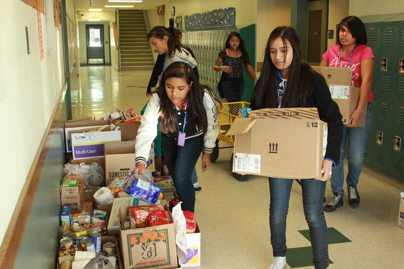 Leadership studentsJennifer Galvan, front left, Aislyn Alonso Flores, and Wendelynn Blevins, with Jalen Widman and Jeni Pineda in back, carry and stack food collected from classrooms.