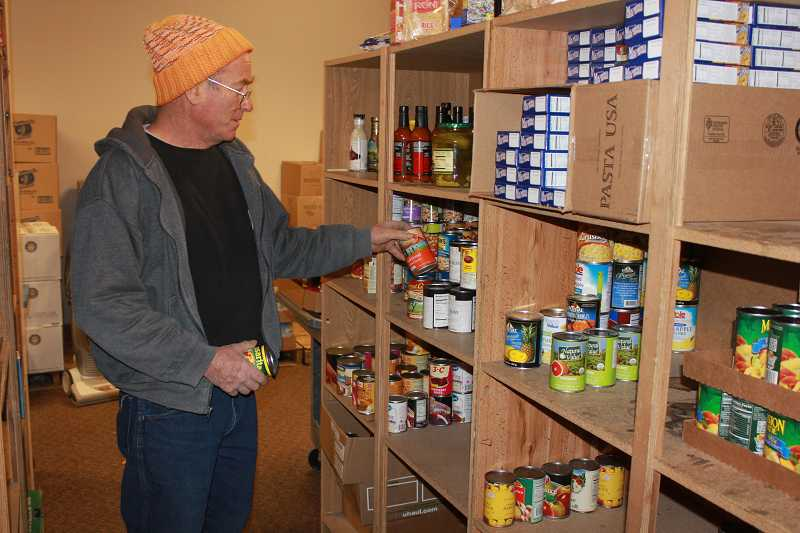 Jefferson County Food Bank Director Paul Rueter restocks shelves with some of the donations.