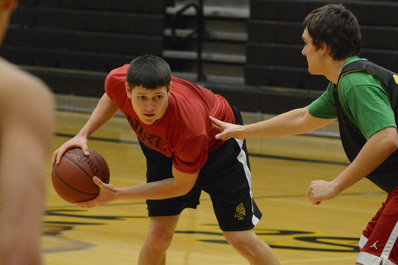 by: JOHN WILLIAM HOWARD - St. Helens senior Tanner Long looks around a defender during practice on Wednesday morning. Long is in his third year as the team's point guard, and will be a major asset toward the squad's success this season.