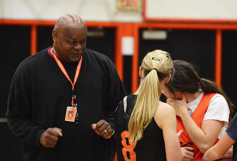 by: JOHN WILLIAM HOWARD - Coach David Spirlin stands head and shoulders over Scappoose seniors Alix Raya (8) and Abby Kessi. Though he has a tough reputation, and the nickname 'The Terminator,' he has earned the team's respect through laughter.