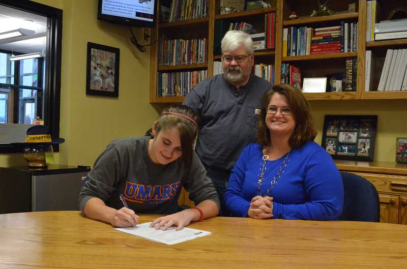 by: JEFF GOODMAN - Colleen Crutchfield signs a letter of intent Nov. 18 at Canby High School to continue her softball career at the University of Mary in North Dakota. She is joined by her parents, Milt and Kathi.
