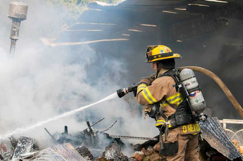 Firefighters tackle a barn fire on Southwest Edy Road in Sherwood, Tuesday morning.