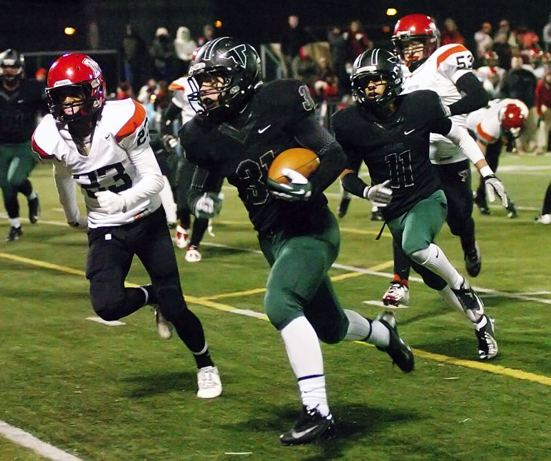 by: DAN BROOD - RUNNING STRONG -- Tigard junior Tyler Walker doesn't let anything get in his way as he scores a touchdown during the Tigers' state playoff quarterfinal victory over North Medford.