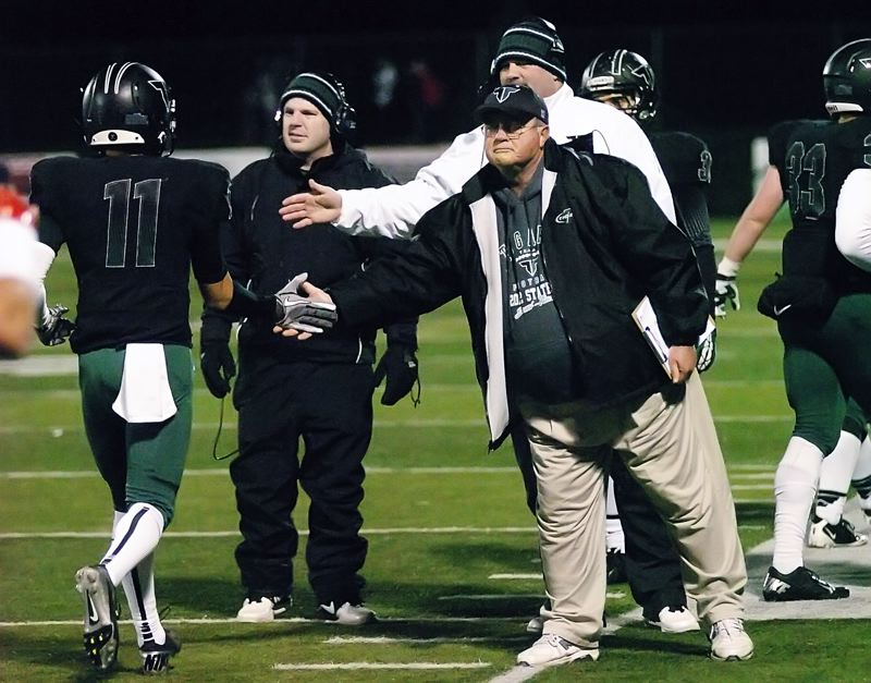 by: DAN BROOD - GOOD JOB -- Tigard head coach Craig Ruecker congratulates Tiger receiver Daren Rodrigues following a touchdown catch in Friday's state playoff quarterfinal victory over North Medford.