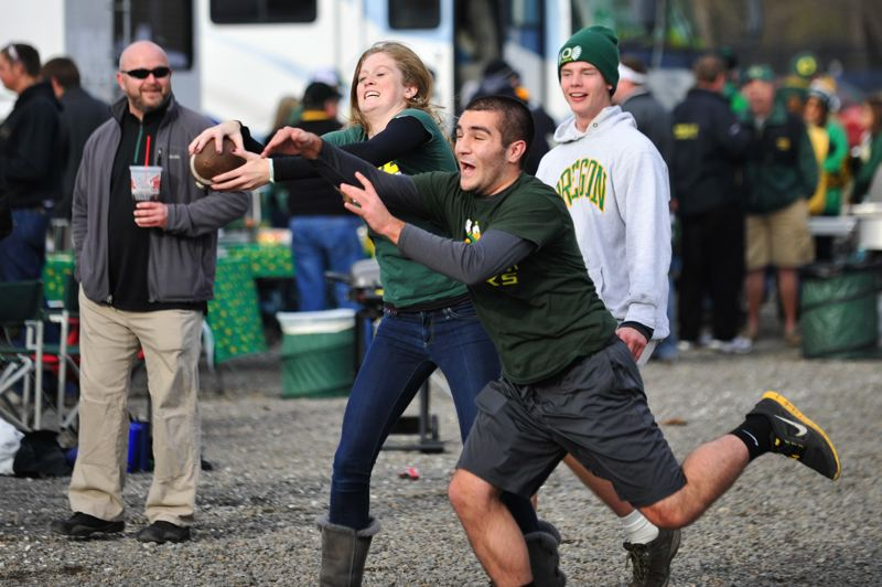 by: COURTESY OF JOHN LARIVIERE - Football of the touch variety and of other sorts is played in the Autzen Stadium parking lot before Friday's rivalry game. Megan Goodling and Kian Safari go for the ball.