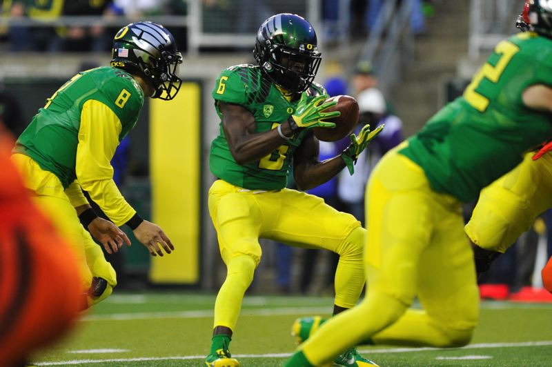 by: COURTESY OF JOHN LARIVIERE - De'Anthony Thomas bobbles a handoff before recovering control in time to score in the first quarter for Oregon.