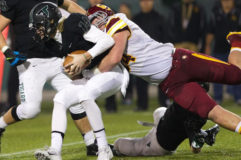 Central Catholic defensive lineman Connor Humphreys tackles Tigard quarterback Jett Even.