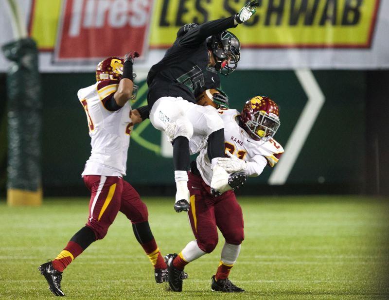 Central Catholic's Tyson Cooper (left) and Aaron Washington (right) upend Tigard tight end Nick Duro.