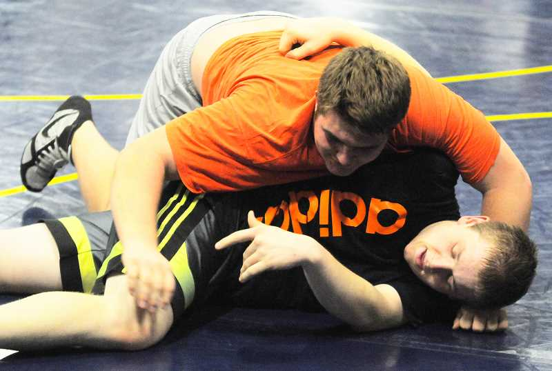 by: LON AUSTIN/CENTRAL OREGONIAN - Jason Williams works to control Trevor Rasmussen during a drill at a recent Crook County High School wrestling practice. Williams is the defending state champion at 285 pounds, while Rasmussen also qualified for the state championships last year. The Cowboys open their season at the Central Oregon Referees Tournament which will be held at Mountain View High School beginning at 10 a.m. Saturday, Dec. 7.