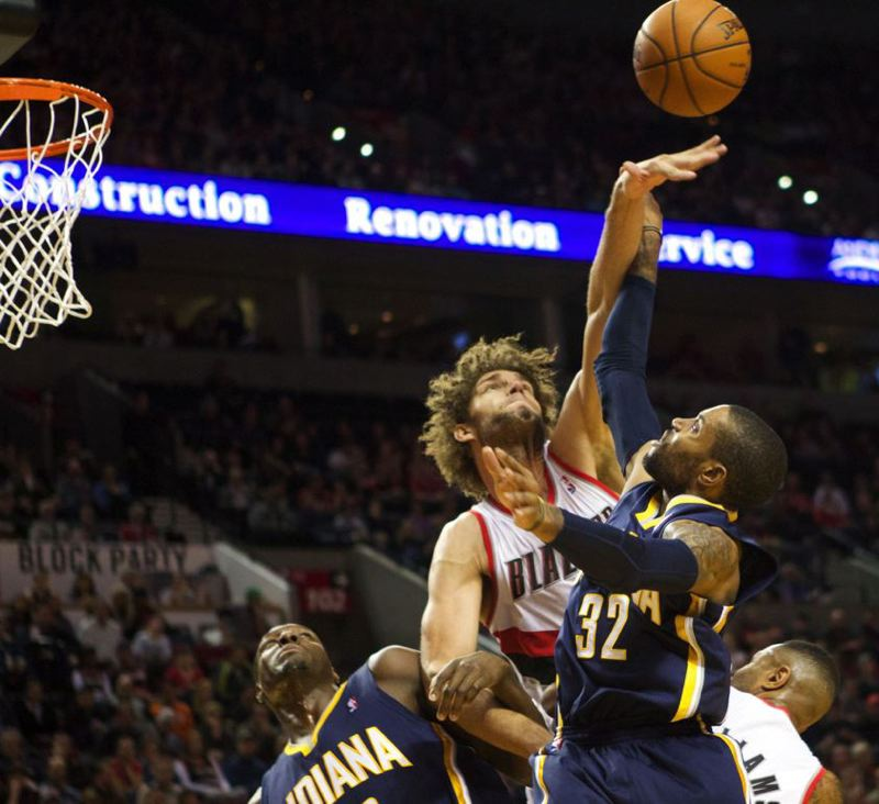 Center Robin Lopez of the Blazers re-directs a shot by CJ Watson of Indiana.