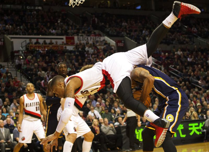 Damian Lillard flies over Indiana's George Hill in the first half.