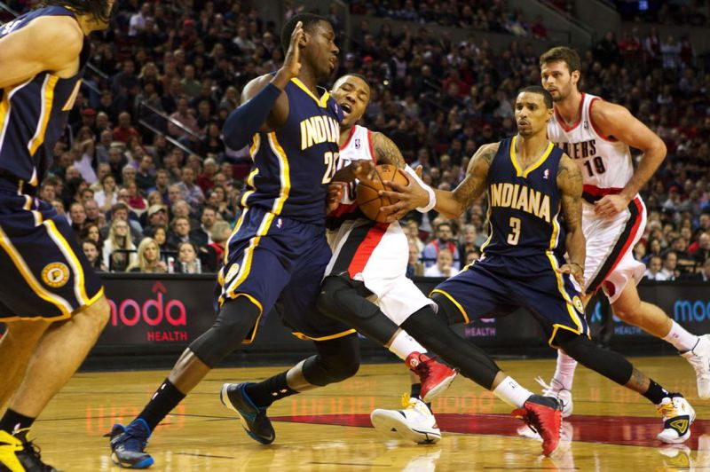 by: TRIBUNE PHOTO: JAIME VALDEZ - Indiana Pacers center Ian Mahinmi blocks the path of Trail Blazers guard Damian Lillard in Portland's homecourt victory Monday night.