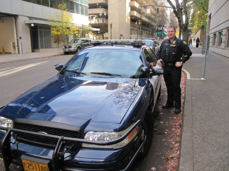 by: KRISTIAN FODEN-VENCIL/OPB - Officer Garrett Dow with his patrol car. Four cameras on the light bar collect number plates of cars as he passes.