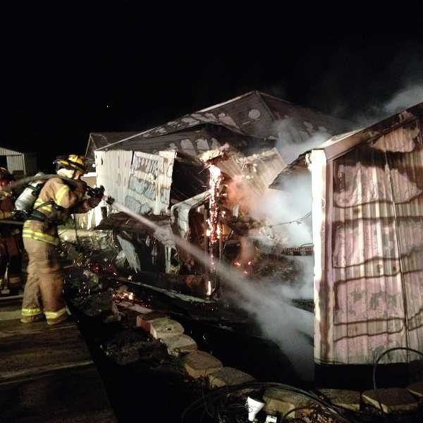 by:  TVF&R - A Tualatin Valley Fire & Rewcue firefighter works on the Nov. 22 fire that destroyed a Stafford-area barn and threatened an adjacent home.