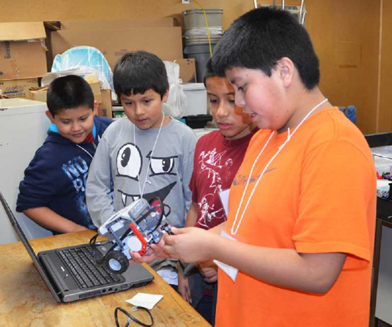 by: MARY STEWART - (From left) Daniel Velazquez, Juan de Jesus, Andrew Nava and Alfredo Alonso, members of the 4-H LEGO Robotics club at Lincoln Elementary,  learn about science, technology, engineering and math by building and running missions with LEGO robots.