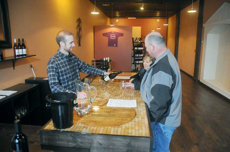 by: GARY ALLEN - In view -- After opening a tasting room four blocks away in 2012, Ancient Wine Cellars has relocated to 718 E. First St. Chris Baker, winemaker, pours a glass for Tom Small during the room's opening Nov. 29.