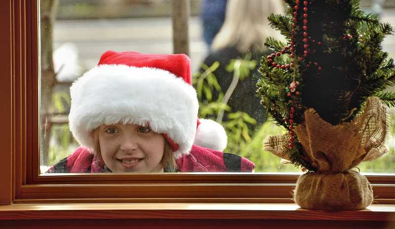 by: TIDINGS FILE PHOTO: VERN UYETAKE - West Linns Kaitlyn Finn takes a peek at Santa through the window of the Willamette Fire Station following the 2012 West Linn holiday parade.