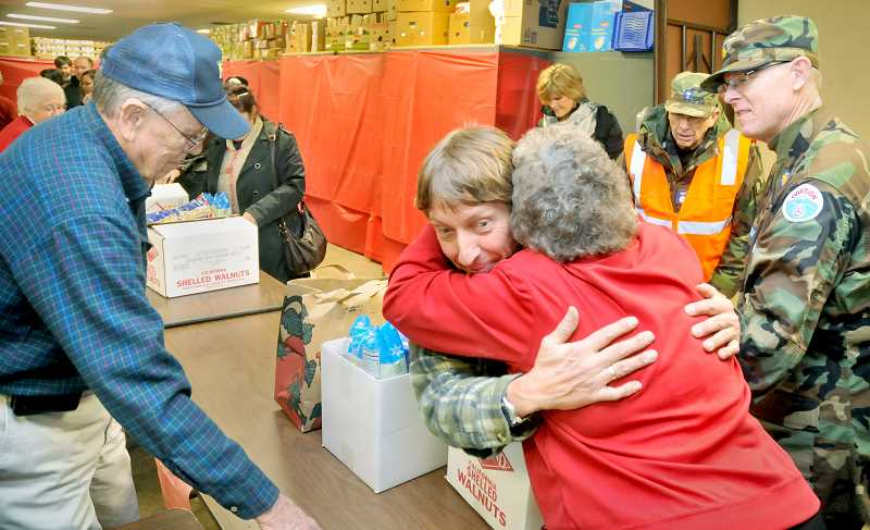 by: GARY ALLEN - Hugs are common when food boxes are meted to individuals and families at F.I.S.H.