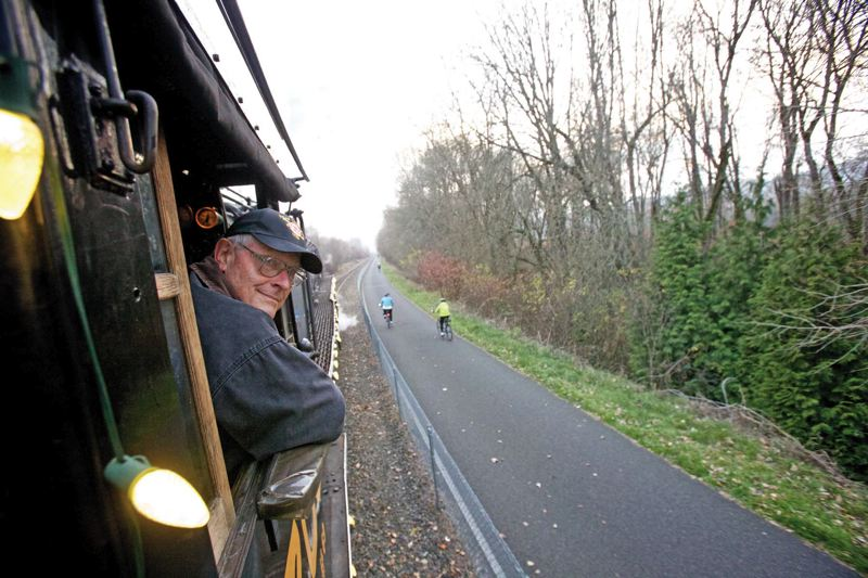 by: TRIBUNE PHOTO: JAIME VALDEZ - SP&S 700 engineer Jim Abney looks at the end of the Holiday Express train during a ride from the Oaks Station at Oaks Amusement Park.