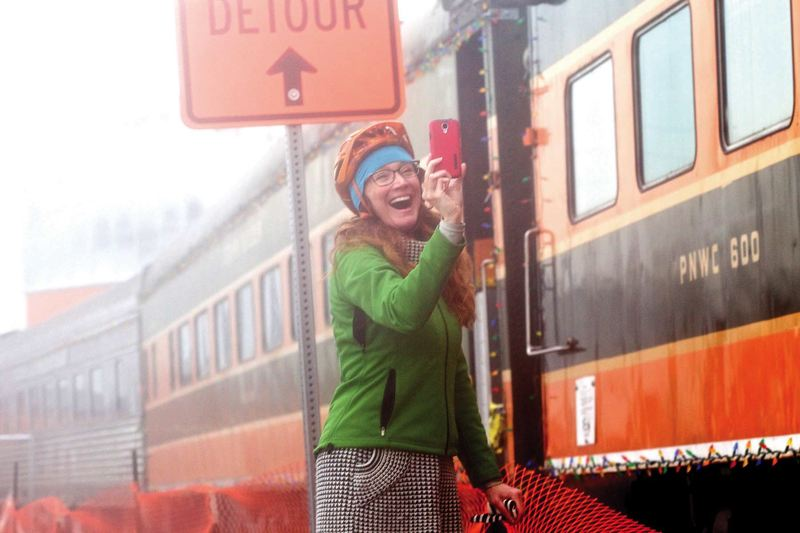 by: TRIBUNE PHOTO: JAIME VALDEZ - Michelle Houck is beside herself as she takes a video on her cell phone of the SP&S 700, departing the Oregon Rail Heritage Center for its first ride on Nov. 29.