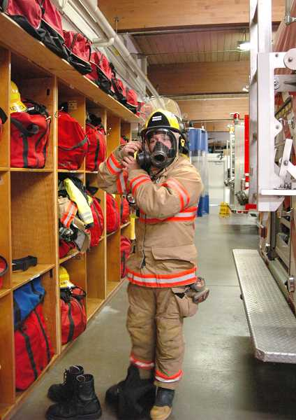 by: ISABEL GAUTSCHI - Firefighter Trent Westenfelt gets suited up in less than a minute.