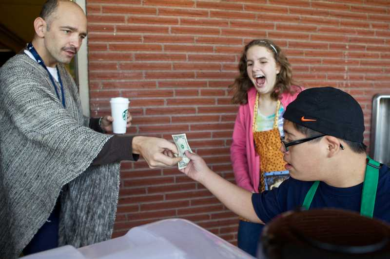 by: PAMPLIN MEDIA GROUP PHOTOS: JAIME VALDEZ - Eighth-grader Irvin Herrera serves coffee cart customer and Lake Oswego Junior High teacher Ian Reeves while another student looks on.
