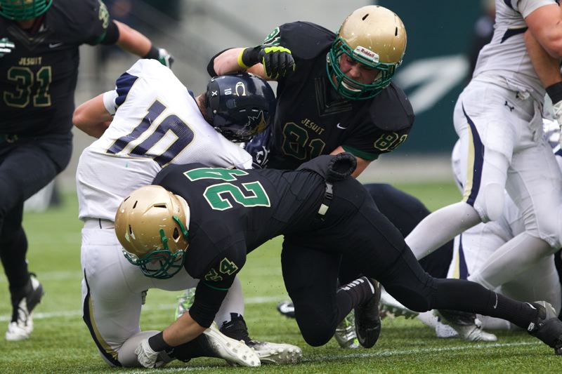 by: TIMES PHOTO: JAIME VALDEZ - Jesuit senior defensive lineman Henry Mondeaux and safety Josh Anderson tackle a Canby ball carrier in the first half of the Crusaders' semifinal win on Saturday