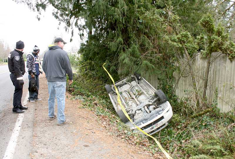 by: PEGGY SAVAGE - Ronnie Granderson, of Molalla, (in ski hat) checks out his vehicle with Molalla Police Officer Aaron Christopherson and a tow truck driver 20 minutes after the crash.