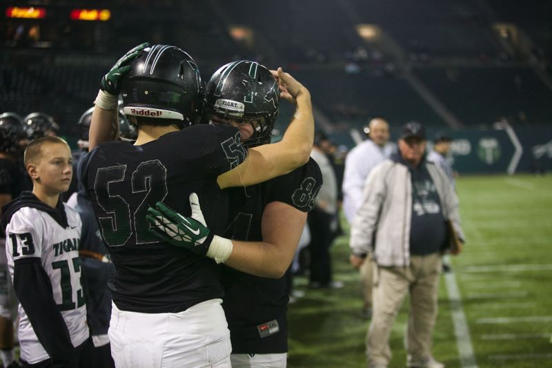 by: JAIME VALDEZ - GREAT SEASON -- Tigard High School seniors Nathan Wick (52) and Jake Biglow embrace near the end of Saturday's Class 6A state playoff semifinal game. The Tigers fell 83-49 to Central Catholic.