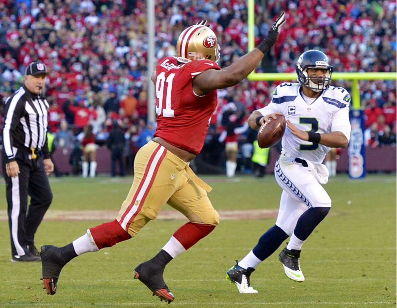 by: COURTESY OF MICHAEL WORKMAN - Defensive lineman Ray McDonald of San Franciscoo pursues Seattle quarterback Russell Wilson.