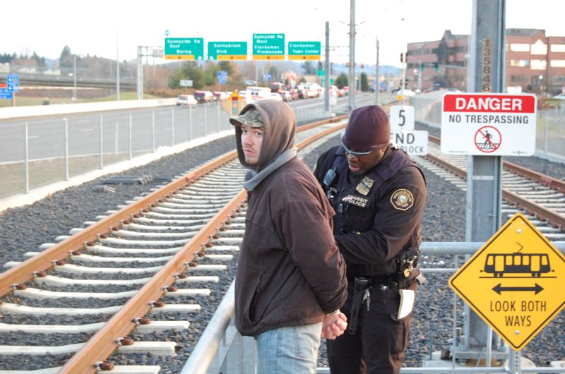 by: PHOTO BY: RAYMOND RENDLEMAN - After checking for valid fare, Transit Police Officer Curtis Brown arrests Nicholas Glendon Davis on an identity-theft charge at the end of the light-rail line at Clackamas Town Center.