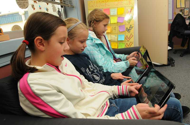 by: PAMPLIN MEDIA GROUP: VERN UYETAKE - The fifth-graders in Tzaddi Bondi's fifth-grade class at Stafford are using iPads to access the programming lessons available during the Hour of Code this week. From left: Morgan Highland, Charlotte Gray and Amanda Myers.