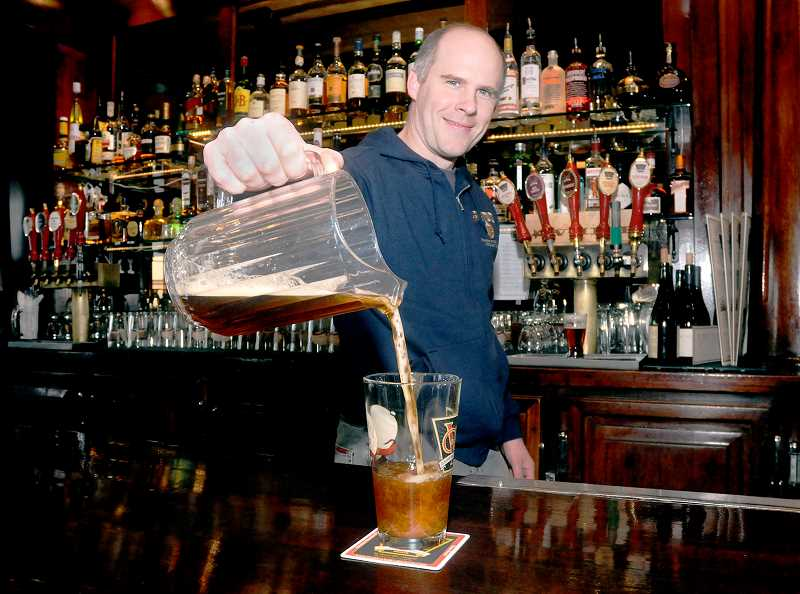 by: GARY ALLEN - Two in one -- Golden Valley Brewery Brew Master Jesse Shue pours a pint of his latest creation, Der Kaffeeklatsch during its unveiling Dec. 5. The coffee-beer is a blend of a dunkel and Guatemala Antigua La Flor from Caravan Coffee in Newberg.