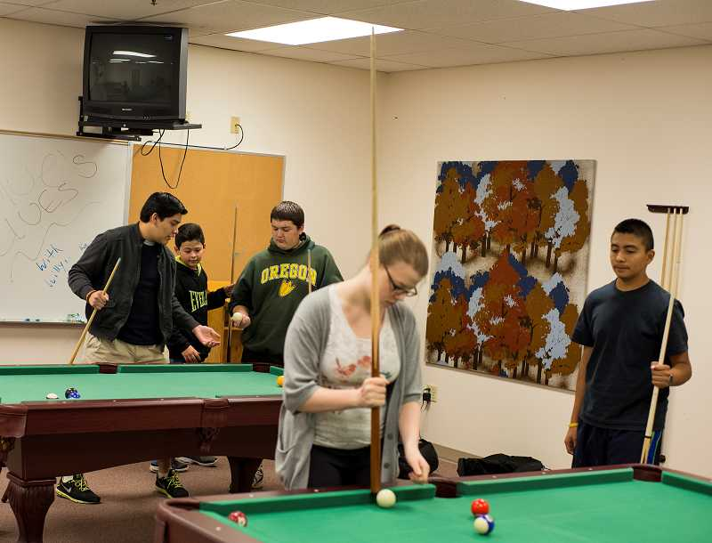 by: NEWS-TIMES PHOTO: CHASE ALLGOOD - Pool, ping pong and video games are available in the recreation room at the Community Learning Center, where students can spend time between class or club time.
