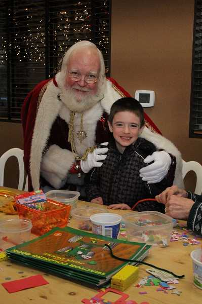 by: LINDSAY KEEFER - Santa Claus visits with Collin Drexel, 6, of Salem, in the kids craft room at the Hazelnut Festival.