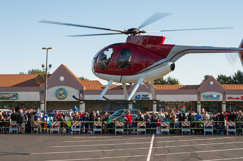 by: GARY BARNES/GTBARNES.COM - Although his reindeer were nowhere to be seen, Santa still made a unique entry into the parking lot of Sherwood Plaza Saturday.