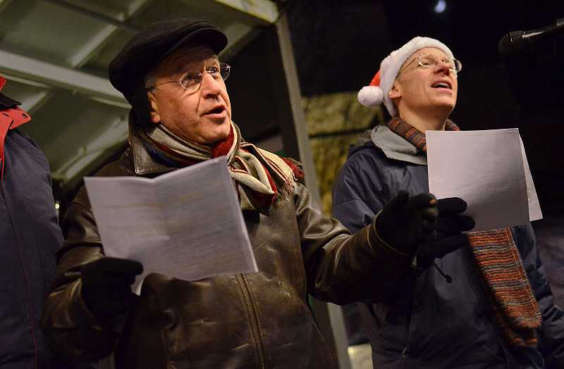 by: TIDINGS PHOTO: VERN UYETAKE - Jeff Liebo, left, and Jim Wiechmann of the West Linn Community Chorus sing holiday favorites prior to Santa's arrival.