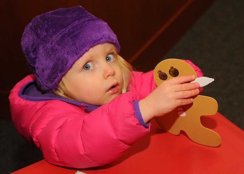by: TIDINGS PHOTO: VERN UYETAKE - Tatum Ray, 2, has fun decorating an ornament.