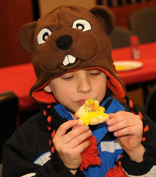 by: TIDINGS PHOTO: VERN UYETAKE - Dylan Smith devours his cookie after quickly decorating it.