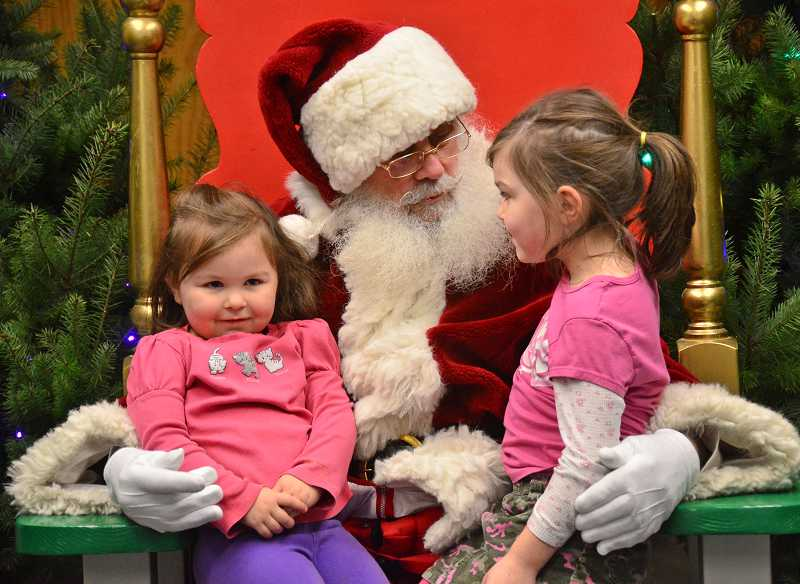 by: TIDINGS PHOTO: VERN UYETAKE - Naiomi, 5, left, and Hannah Griggs, 3, give Santa their wish lists.